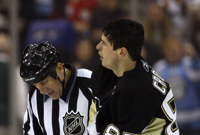 PITTSBURGH, PA - OCTOBER 31:  Sidney Crosby #87 of the Pittsburgh Penguins is escorted off ice by a linesman after fighting with Marek Zidlicky #3 of the Minnesota Wild in the second period at Mellon Arena on October 31, 2009 in Pittsburgh, Pennsylvania.