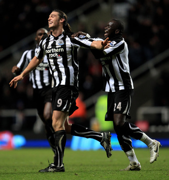 NEWCASTLE UPON TYNE, ENGLAND - DECEMBER 11:  Andy Carroll of Newcastle United celebrates scoring his team's third goal with team mate Cheik Tiote (R) during the Barclays Premier League match between Newcastle United and Liverpool at St James' Park on Dece