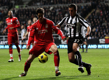 NEWCASTLE UPON TYNE, ENGLAND - DECEMBER 11:  Fernando Torres of Liverpool competes for the ball with Steven Taylor of Newcastle United during the Barclays Premier League match between Newcastle United and Liverpool at St James' Park on December 11, 2010 i
