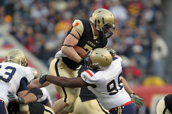 PHILADELPHIA - DECEMBER 11: Running back Jared Hassin #7 of the Army Black Knights is tackled by defensive end Jabaree Tuani #98 of the Navy Midshipmen during a game on December 11, 2010 at Lincoln Financial Field in Philadelphia, Pennsylvania. The Midshi