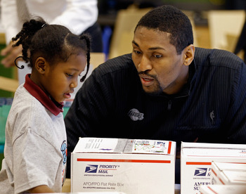 WASHINGTON, DC - DECEMBER 13:  (AFP OUT) Los Angeles Lakers forward Ron Artest (R) helps children volunteers fill care packages during a NBA Cares service event at the Boys and Girls Club at THEARC   December 13, 2010 in Washington, DC. Bryant and all the