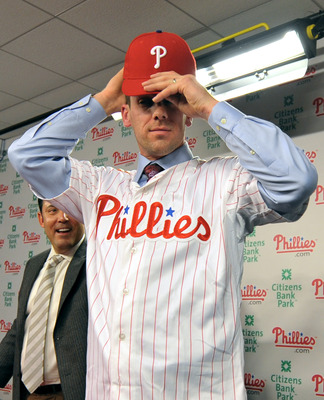 PHILADELPHIA - DECEMBER 15: Pitcher Cliff Lee #33 of the Philadelphia Phillies adjusts his hat after being introduced to the media during a press conference as Philadelphia Phillies general manager Ruben Amaro Jr. (L) looks on at Citizens Bank Park on Dec
