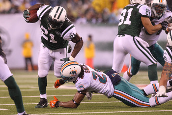 EAST RUTHERFORD, NJ - DECEMBER 12:  LaDainian Tomlinson #21 of the New York Jets is tackled by Sean Smith #24 of the Miami Dolphins at New Meadowlands Stadium on December 12, 2010 in East Rutherford, New Jersey.  (Photo by Nick Laham/Getty Images)