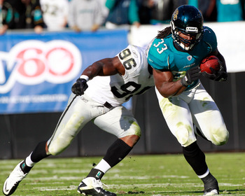 JACKSONVILLE, FL - DECEMBER 12:  Kamerion Wimbley #96 of the Oakland Raiders attempts to tackle Greg Jones #33 of the Jacksonville Jaguars runs during the game at EverBank Field on December 12, 2010 in Jacksonville, Florida.  (Photo by Sam Greenwood/Getty