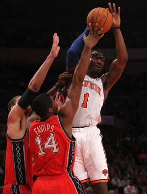 NEW YORK, NY - NOVEMBER 30:  Amar'e Stoudemire #1 of the New York Knicks is double teamed by Brook Lopez #11 and Derrick Favors #14 of the New Jersey Nets on November 30, 2010 at Madison Square Garden in New York City. NOTE TO USER: User expressly acknowl