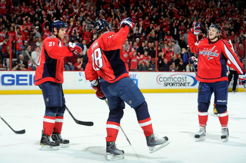 WASHINGTON - NOVEMBER 26:  Alexander Semin #8 of the Washington Capitals celebrates with Brooks Laich #21 and John Carlson #74 after scoring a hat trick in the second period against the Tampa Bay Lightning  at the Verizon Center on November 26, 2010 in Wa