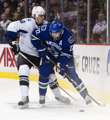 VANCOUVER, CANADA - DECEMBER 11: Daniel Sedin #22 of the Vancouver Canucks tries to fight off Randy Jones #8 of the Tampa Bay Lightning during the second period in NHL action on December 11, 2010 at Rogers Arena in Vancouver, BC, Canada.  (Photo by Rich L