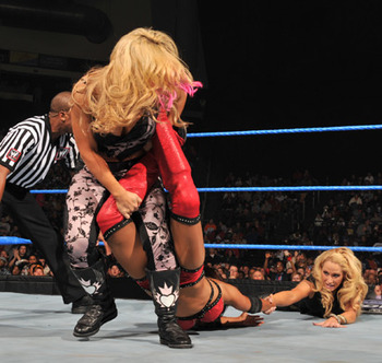Natalya puts the sharpshooter on Layla and Michelle tries to help her partner, photo copyright to WWE.com