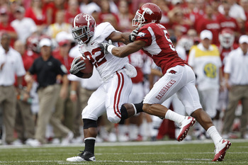 FAYETTEVILLE - SEPTEMBER 25: Mark Ingram #22 of the Alabama Crimson Tide pushes away a tackle attempt by Tramain Thomas #5 of the Arkansas Razorbacks during a first half touchdown run at Donald W. Reynolds Razorback Stadium on September 25, 2010 in Fayett