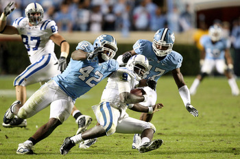 CHAPEL HILL, NC - NOVEMBER 07:  Thaddeus Lewis #9 of the Duke Blue Devils is sacked by Robert Quinn #42 of the North Carolina Tar Heels during their game at Kenan Stadium on November 7, 2009 in Chapel Hill, North Carolina.  (Photo by Streeter Lecka/Getty