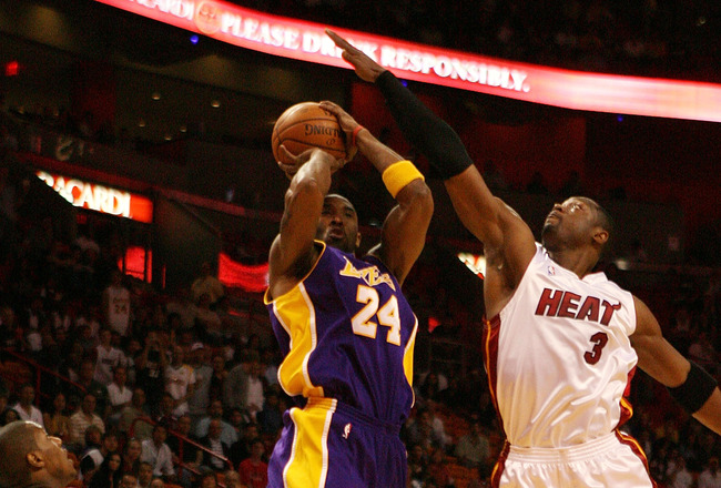 MIAMI - DECEMBER 19:  Kobe Bryant #24 of the Los Angeles Lakers has his shot altered by the defense of Dwyane Wade #3 and Mario Chalmers #6 of the Miami Heat at American Airlines Arena on December 19, 2008 in Miami, Florida. NOTE TO USER: User expressly a