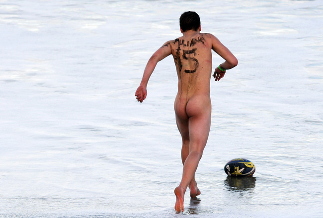 DUNEDIN, NEW ZEALAND - JULY 12: (EDITORS NOTE: NUDITY) A naked rugby player retrieves the ball from the surf during a nude rugby game at St Kilda Beach on July 12, 2008 in Dunedin, New Zealand. The nude rugby match on the beach is a traditional prelude to
