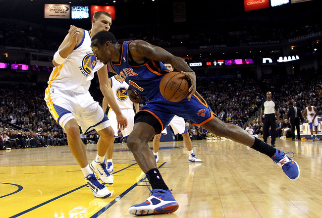 OAKLAND, CA - NOVEMBER 19:  Amar'e Stoudemire #1 of the New York Knicks dribbles past Andris Biedrins #15 of the Golden State Warriors at Oracle Arena on November 19, 2010 in Oakland, California. NOTE TO USER: User expressly acknowledges and agrees that,