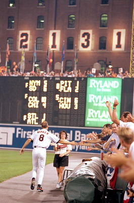 BALTIMORE - SEPTEMBER 6:  Cal Ripken Jr. #8 of the Baltimore Orioles high-fives fans along side the warning track as he celebrates breaking Lou Gehrig's record for consecutive game played with his 2131 career game, during a game against the California Ang