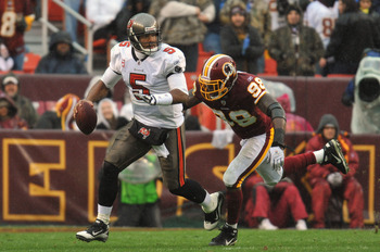 LANDOVER, MD - DECEMBER 12:  Josh Freeman #5 of the Tampa Bay Buccaneers is chased by Brian Orakpo #98 of the Washington Redskins at FedExField on December 12, 2010 in Landover, Maryland. The Redskins led the Buccaneers at the half 10-3 00-00. (Photo by L