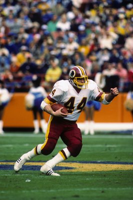 WASHINGTON - NOVEMBER 20:  Running back John Riggins #44 of the Washington Redskins runs up field with the ball during the game against the Los Angeles Rams at RFK Stadium on November 20, 1983 in Washington, D.C.  The Redskins won 42-20.  (Photo by George