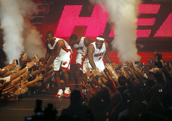 MIAMI - JULY 09:  Fans cheer as (L-R) Dwyane Wade #3, Chris Bosh #1 and LeBron James #6 of the Miami Heat are introduced during a welcome party at American Airlines Arena on July 9, 2010 in Miami, Florida.  (Photo by Marc Serota/Getty Images)