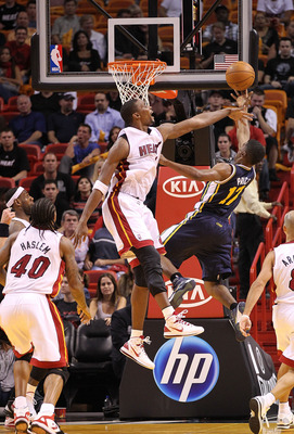 MIAMI - NOVEMBER 09: Chris Bosh #1 of the Miami Heat blocks the shot of Earl Watson #11 during a game against the Utah Jazz at American Airlines Arena on November 9, 2010 in Miami, Florida. NOTE TO USER: User expressly acknowledges and agrees that, by dow