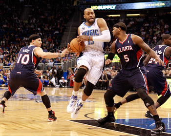 ORLANDO, FL - DECEMBER 06:  Vince Carter #15 of the Orlando Magic drives between Mike Bibby #10 and Josh Smith #5 of the Atlanta Hawks during the game at Amway Arena on December 6, 2010 in Orlando, Florida. NOTE TO USER: User expressly acknowledges and ag