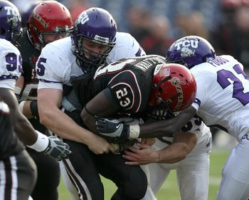 SAN DIEGO - NOVEMBER 7:  Defensive lineman D.J. Yendrey #55 of  the Texas Christian University Horned Frogs tackles runing back Brandon Sullivan #23 of the San Diego State Aztecs on November 7, 2009 at Qualcomm Stadium in San Diego, California.   TCU won