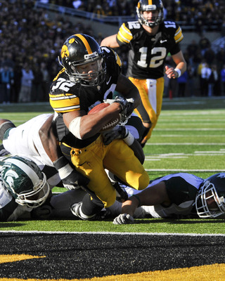 IOWA CITY, IA - OCTOBER 30: Running back Adam Robinson #32 of the University of Iowa Hawkeyes dives into the end zone past Michigan State Spartan defenders for a touch down as quarterback Ricky Stanzi #12 watches on during the first half of play at Kinnic