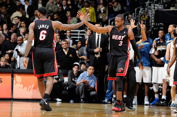 WASHINGTON - DECEMBER 18:  LeBron James #6 congratulates Dwyane Wade #3 after drawing a foul in the fourth quarter against the Washington Wizards at the Verizon Center on December 18, 2010 in Washington, DC. NOTE TO USER: User expressly acknowledges and a