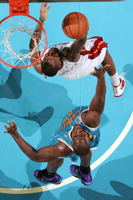 NEW ORLEANS - OCTOBER 13:  Kenny Hasbrouck #4 of the Miami Heat grabs a rebound over Emeka Okafor #50 of the New Orleans Hornets at the New Orleans Arena on October 13, 2010 in New Orleans, Louisiana.  NOTE TO USER: User expressly acknowledges and agrees