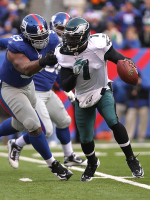 EAST RUTHERFORD, NJ - DECEMBER 19:  Michael Vick #7 of the Philadelphia Eagles runs from the tackle of Chris Canty #99 of the New York Giants at New Meadowlands Stadium on December 19, 2010 in East Rutherford, New Jersey.  (Photo by Nick Laham/Getty Image