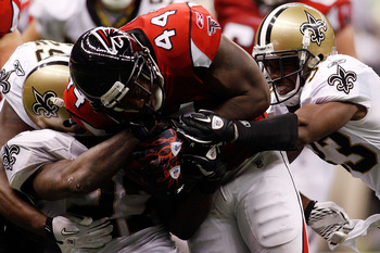 NEW ORLEANS - SEPTEMBER 26:  Jason Snelling #44 of the Atlanta Falcons is tackled by Malcom Jenkins #27 and Jabari Greer #33 of the New Orleans Saints at the Louisiana Superdome on September 26, 2010 in New Orleans, Louisiana.  The Falcons defeated the Sa