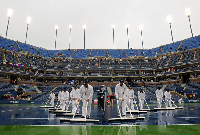 NEW YORK - SEPTEMBER 12:  Ground crew workers try to dry the court during a rain delay on day fourteen of the 2010 U.S. Open at the USTA Billie Jean King National Tennis Center on September 12, 2010 in the Flushing neighborhood of the Queens borough of Ne