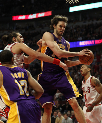CHICAGO, IL - DECEMBER 10: Pau Gasol #16 of the Los Angeles Lakers pulls down a rebound in front of Joakim Noah #13 of the Chicago Bulls at the United Center on December 10, 2010 in Chicago, Illinois. The Bulls defeated the Lakers 88-84. NOTE TO USER: Use