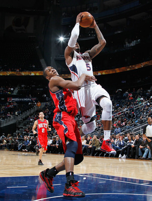ATLANTA, GA - DECEMBER 07:  Derrick Favors #14 of the New Jersey Nets fouls Josh Smith #5 of the Atlanta Hawks at Philips Arena on December 7, 2010 in Atlanta, Georgia.  NOTE TO USER: User expressly acknowledges and agrees that, by downloading and/or usin