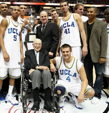 ANAHEIM, CA - DECEMBER 13:  Former coach John Wooden poses together with the UCLA Bruins team, head coach Ben Howland and great grandson Tyler Trapani #4 after the John R. Wooden Classic game against the DePaul Blue Demons at Honda Center on December 13,