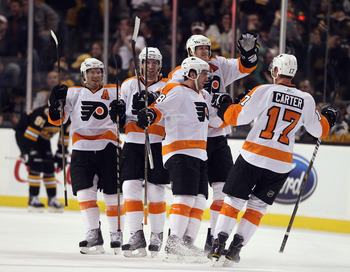 BOSTON, MA - DECEMBER 11:  Mike Richards #18 of the Philadelphia Flyers is congratulated by teammates Chris Pronger #20, Andreas Nodl #15, Kimmo Timonen #44 and Jeff Carter #17 after Richards scored the game winning goal in overtime against the Boston Bru