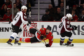 CHICAGO, IL - DECEMBER 15: Troy Brouwer #22 of the Chicago Blackhawks falls to the ice between Adam Foote #52 and Greg Mauldin #20 of the Colorado Avalanche at the United Center on December 15, 2010 in Chicago, Illinois. (Photo by Jonathan Daniel/Getty Im