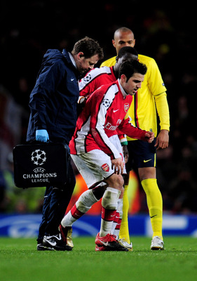 LONDON, ENGLAND - MARCH 31:  Cesc Fabregas of Arsenal hobbles off the pitch injured to receive treatment after levelling the scores at 2-2 from the penalty spot during the UEFA Champions League quarter final first leg match between Arsenal and FC Barcelon