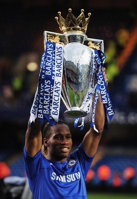 LONDON, ENGLAND - MAY 09:  Didier Drogba of Chelsea celebrates with the trophy as they win the title after the Barclays Premier League match between Chelsea and Wigan Athletic at Stamford Bridge on May 9, 2010 in London, England. Chelsea won 8-0 to win th