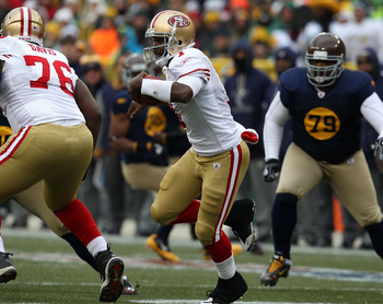 GREEN BAY, WI - DECEMBER 05: Troy Smith #1 of the San Francisco 49ers runs past teammate Anthony Davis #76 as Ryan Pickett #79 of the Green Bay Packers pursues the play at Lambeau Field on December 5, 2010 in Green Bay, Wisconsin. The Packers defeated the