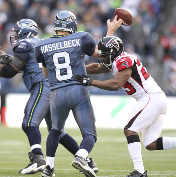 SEATTLE, WA - DECEMBER 19:  Quarterback Matt Hasselbeck #8 of the Seattle Seahawks is hit as he passes by Brian Williams #29 of the Atlanta Falcons at Qwest Field on December 19, 2010 in Seattle, Washington. The Falcons defeated the Seahawks 34-18. (Photo