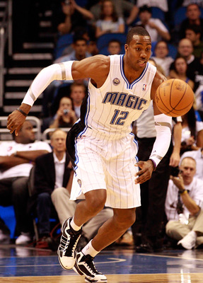 ORLANDO, FL - DECEMBER 18:  Dwight Howard #12 of the Orlando Magic chases down a loose ball during the game against the Philadelphia 76ers at Amway Arena on December 18, 2010 in Orlando, Florida.  NOTE TO USER: User expressly acknowledges and agrees that,