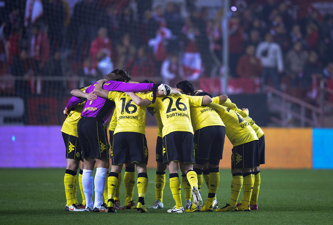 SEVILLE, SPAIN - DECEMBER 15:  Borussia Dortmund players hug themselves prior the UEFA Europa League group J match between Sevilla and Borussia Dortmund at Estadio Ramon Sanchez Pizjuan on December 15, 2010 in Seville, Spain. The match ended 2-2. (Photo b