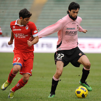 BARI, ITALY - DECEMBER 19:  Javier Pastore (R) of Palermo holds off the challenge from Emanuel Banito Rivas of Bari during the Serie A match between Bari and Palermo at Stadio San Nicola on December 19, 2010 in Bari, Italy.  (Photo by Tullio M. Puglia/Get