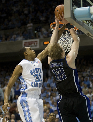 CHAPEL HILL, NC - FEBRUARY 10: Duke forward Kyle Singler #12 works to shoot the ball against North Carolina forward John Henson #31 during a men's college basketball game at Dean Smith Center on February 10, 2010 in Chapel Hill, North Carolina. (Photo by