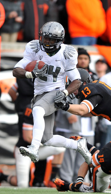 CORVALLIS, OR - DECEMBER 4: Kenjon Barner #24 of the Oregon Ducks avoids the tackle of Rueben Robinson #13 of the Oregon State Beavers in the second quarter of the game at Reser Stadium on December 4, 2010 in Corvallis, Oregon. (Photo by Steve Dykes/Getty