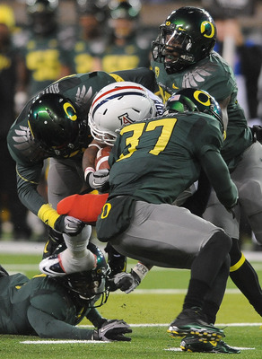 EUGENE, OR - NOVEMBER 26: Running back Nic Grigsby #5 of the Arizona Wildcats is tackled by cornerback Talmadge Jackson III #37 and safety John Boyett #20 of the Oregon Ducks in the fourth quarter of the game at Autzen Stadium on November 26, 2010 in Euge