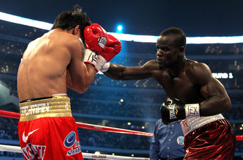 ARLINGTON, TX - MARCH 13:  (R-L) Joshua Clottey of Ghana throws a right to the face of Manny Pacquiao of the Philippines during the WBO welterweight title fight at Cowboys Stadium on March 13, 2010 in Arlington, Texas.  (Photo by Jed Jacobsohn/Getty Image