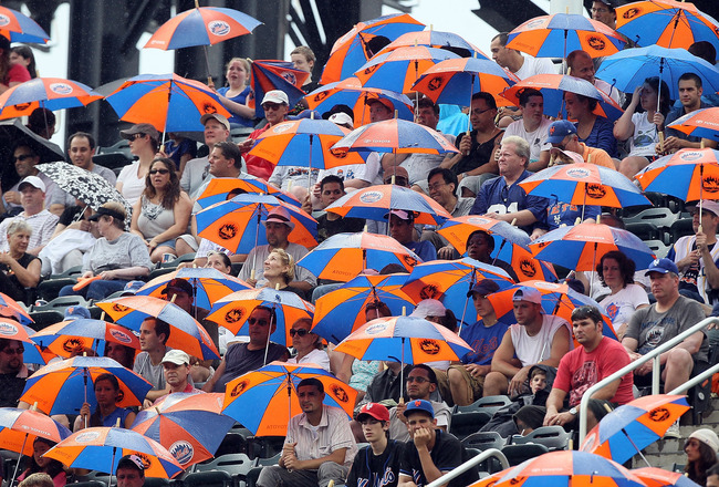 NEW YORK - JULY 29:  Fans break out promotional umbrellas as rain starts to fall as the New York Mets play against the St. Louis Cardinals on July 29, 2010 at Citi Field in the Flushing neighborhood of the Queens borough of New York City. The Mets defeate