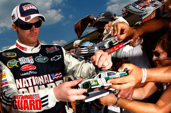 BROOKLYN, MI - AUGUST 14:  Dale Earnhardt Jr., driver of the #88 AMP Energy/National Guard Chevrolet, signs autographs for fans after qualifying for the NASCAR Sprint Cup Series Michigan 400 at Michigan Internetional Speedway on August 14, 2009 in Brookly