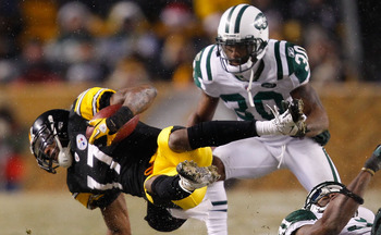 PITTSBURGH - DECEMBER 19:  Mike Wallace #17 of the Pittsburgh Steelers is tripped up by members of the New York Jets defense after catching a pass during the game on December 19, 2010 at Heinz Field in Pittsburgh, Pennsylvania.  (Photo by Jared Wickerham/