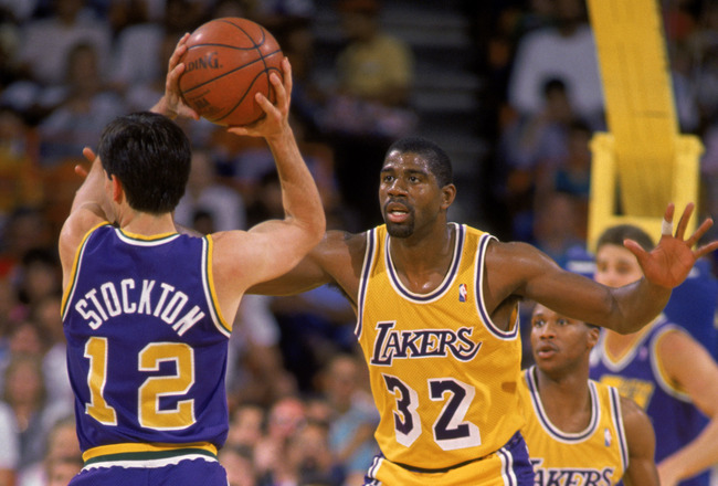 LOS ANGELES - 1987:  Magic Johnson #32 of the Los Angeles Lakers guards John Stockton #12 of the Utah Jazz during an NBA game at the Great Western Forum in Los Angeles, California in 1987. (Photo by: Stephen Dunn/Getty Images)